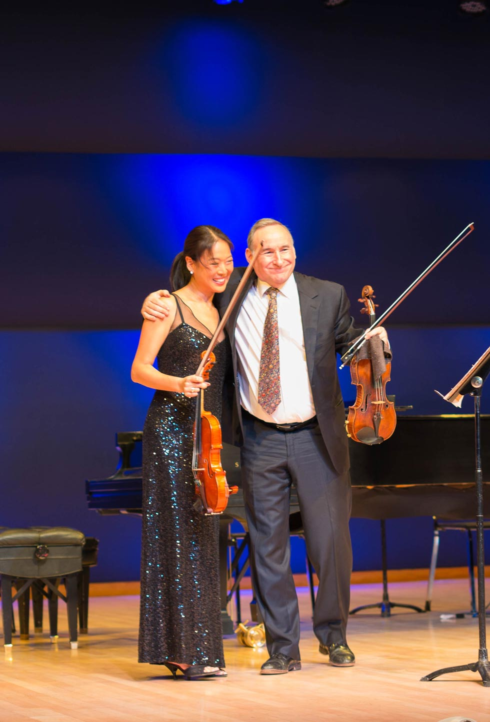 two violinists receiving applause after performance